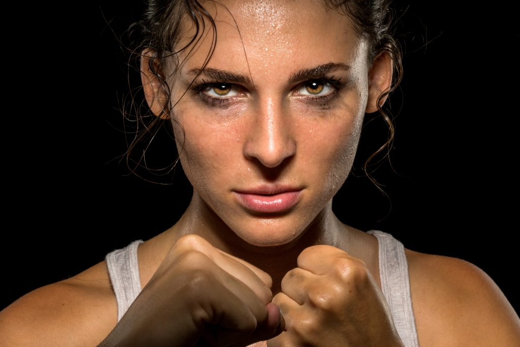 Intense female fighter stare with fist up in self defense training, powerful and confident